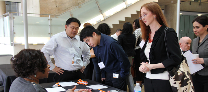 A student talking to a company representative while other students wait in line behind her at Career Day