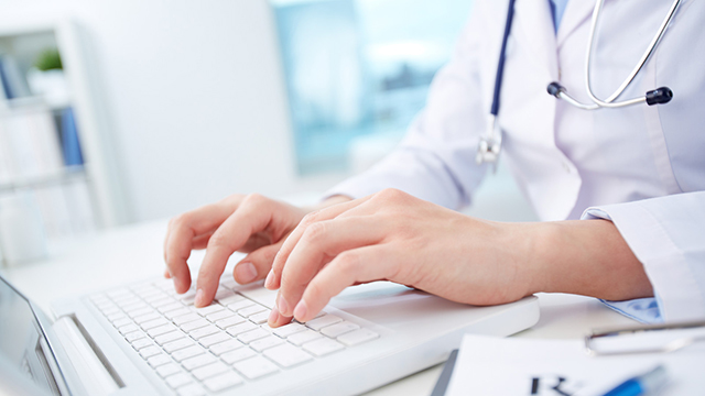 An image of a person typing on a laptop in a health care setting